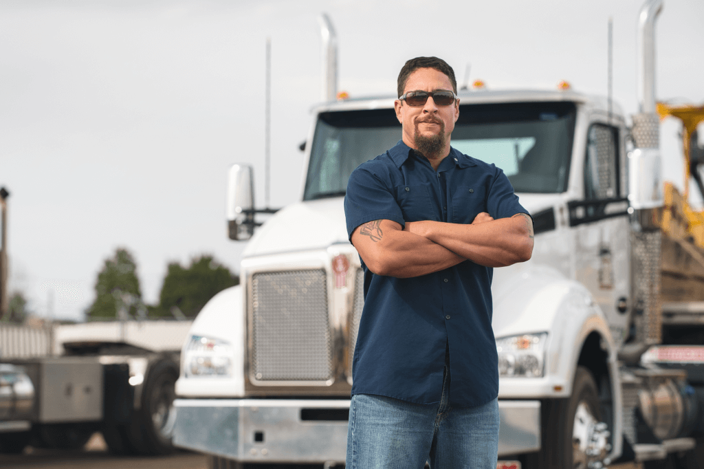 Person with crossed arms stands with truck in the background.