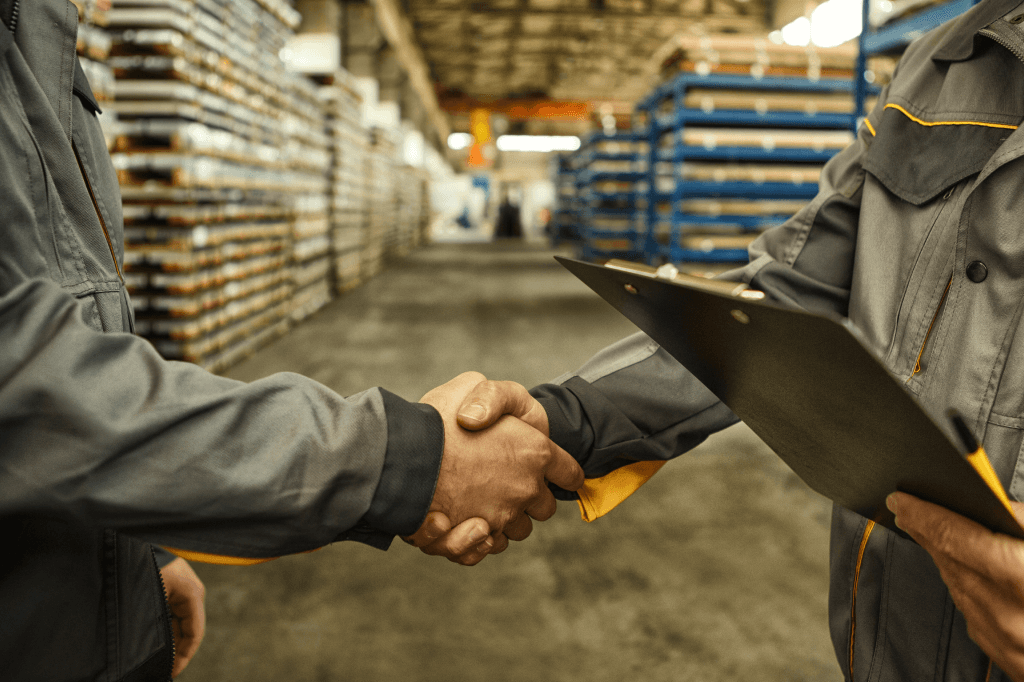 Two people shaking hands in a room with stacked pallets