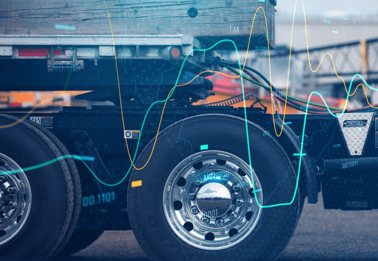Close-up of fifth-wheel section and tires from the side with trailer connected.