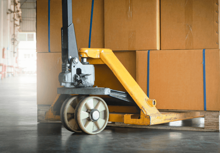 a pallet jack positioned to move a pallet of boxes.