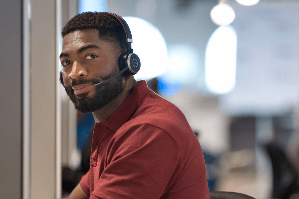 Seated bearded man wearing headset and slightly smiling
