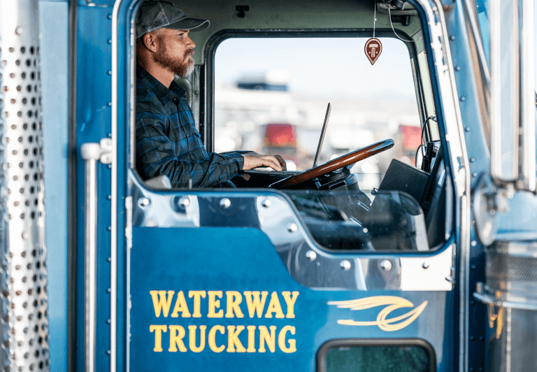 a seated man in the driver seat viewed through the passenger window of a truck