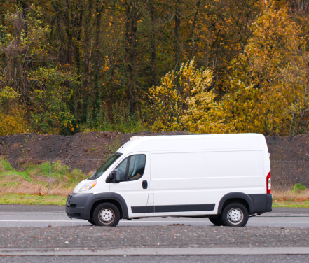 Cargo van driving on a country road.