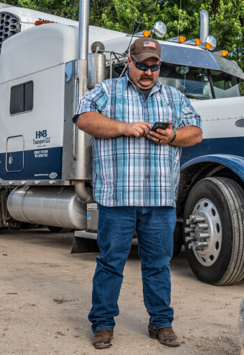 Shane Higgins, Truckstop.com customer, using his smartphone to find and book loads on the load board for his dry vans.