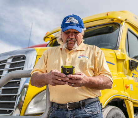 Ernie Hall, a Truckstop.com customer, using the load board app to find loads for his yellow dry van, which is behind him.