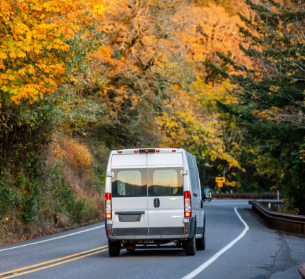 A sprinter van drives down the road among the fall leaves.