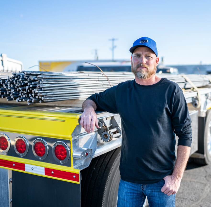 Carrier standing in front of his flatbed trailer loaded with rebar.