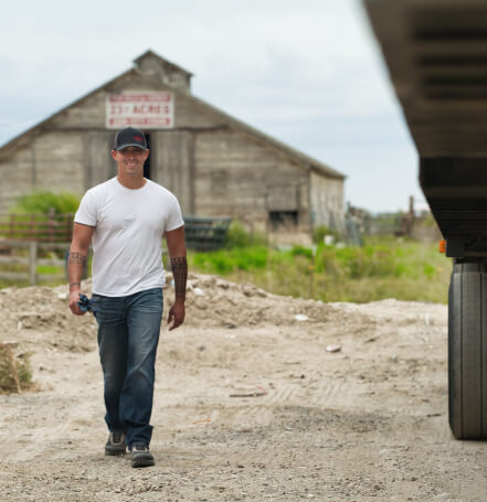 Truckstop.com customer walks to his truck with a large barn in the background.