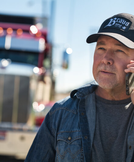 carrier talks on the phone and looks into the distance with his truck visible in the background