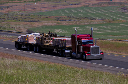 Red tractor with flat bed hauling two trailers ful of different freight.