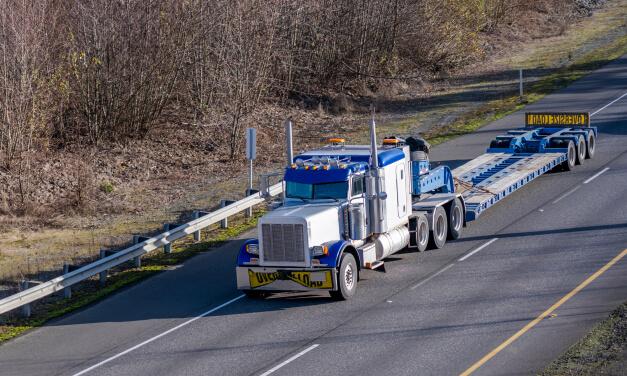 A blue tractor pulls an empty low boy trailer