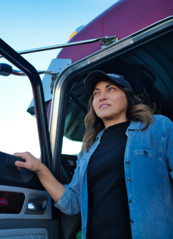 A truck driver steps out of her cab and looks out into the distance.
