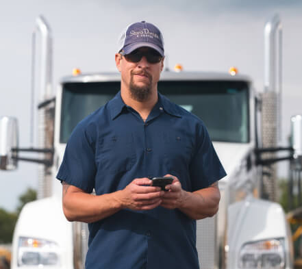 Carrier standing in front of his truck using the Truckstop.com mobile app.