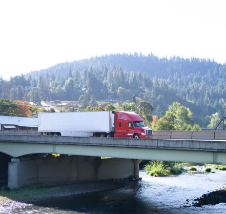 Red tractor with refer trailer crossing a bridge in the mountains.