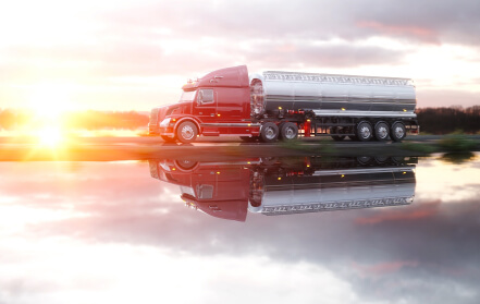 Tanker truck drives past a body of water as the sun sets.