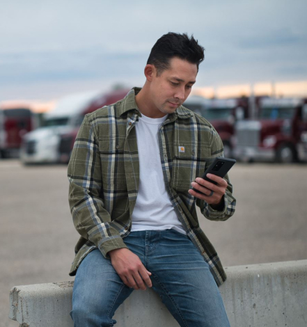 A trucker driver checks his Truckstop.com app while at the truck stop.