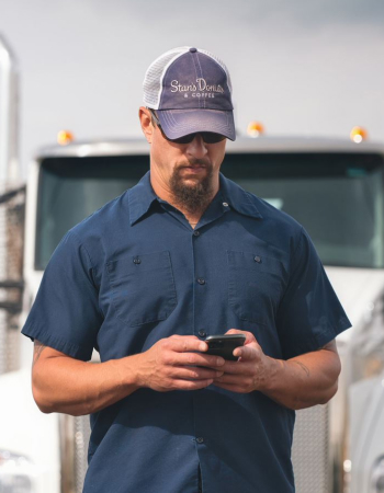 A truck driver uses his phone to find expedited loads on Truckstop.com.